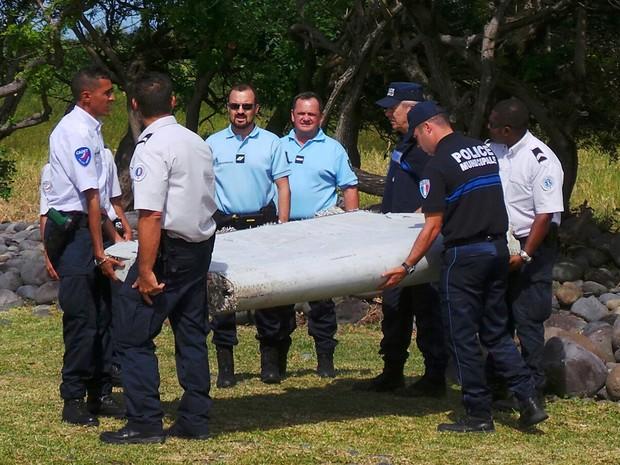 Foto de 29/07 mostra policiais carregando peça de avião encontrada na ilha de Reunião, no Oceano Índico. O primeiro-ministro da Malásia confirmou nesta quarta (05) que a peça pertence ao voo MH370 da Malaysia Airlines, desaparecido em março de 2014 (Foto:  Prisca Bigot/Zinfos974/Reuters/Arquivo)
