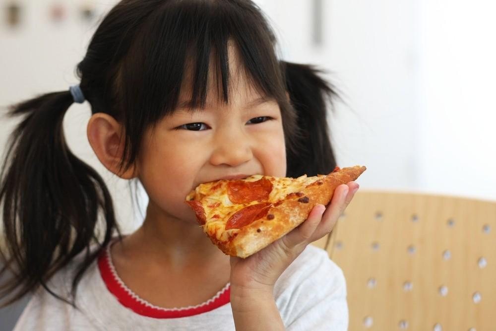 Criança comendo um pedaço de pizza (Foto: Shutterstock)