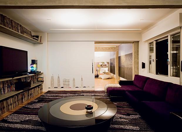 O estúdio do DJ, que também é home theater, é isolado do restante da sala pela porta de correr, que recebeu adesivos de prédios de São Paulo. No sofá, manta do Empório Beraldin. Tapete da Avanti. Mesa de centro da Micasa (Foto: Maíra Acayaba)