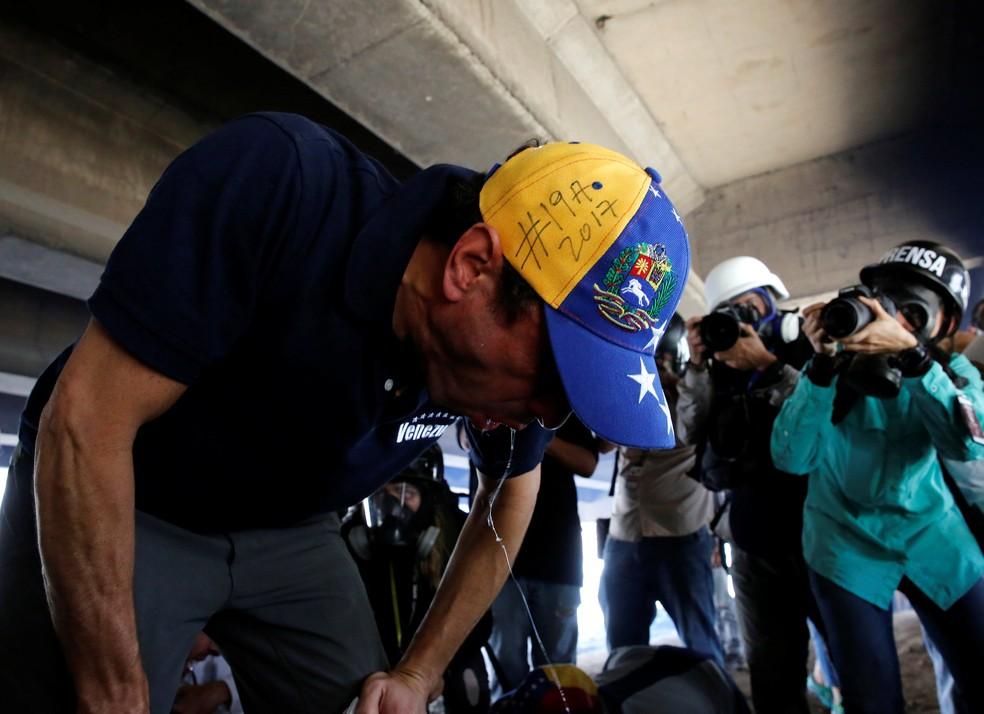 Líder opositor e governador de Miranda, Henrique Capriles, reage após polícia soltar gás lacrimogêneo durante protesto nesta quarta-feira (19) em Caracas (Foto: REUTERS/Marco Bello)