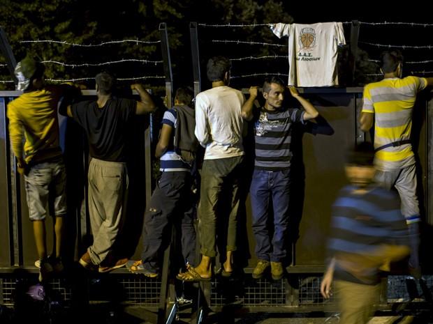 Migrantes se apoiam em barreira na fronteira com a Hungria, perto da vila de Horgos, na Sérvia, na terça (15) (Foto: Reuters/Marko Djurica)
