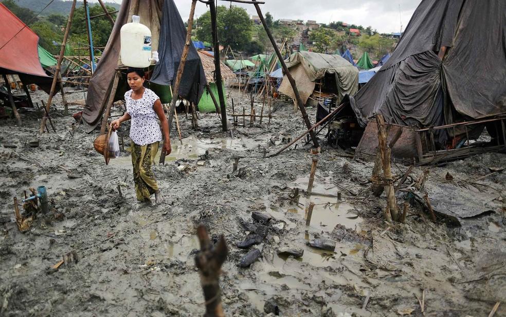Mulher atravessa lamaçal do campo de extração em Minhla com um galão de água limpa equilibrado sobre sua cabeça. Em Mianmar, país em que a maioria da população vive na pobreza, comunidades encontram maneiras de explorar as riquezas minerais do solo. (Foto: Damir Sagolj/Reuters)