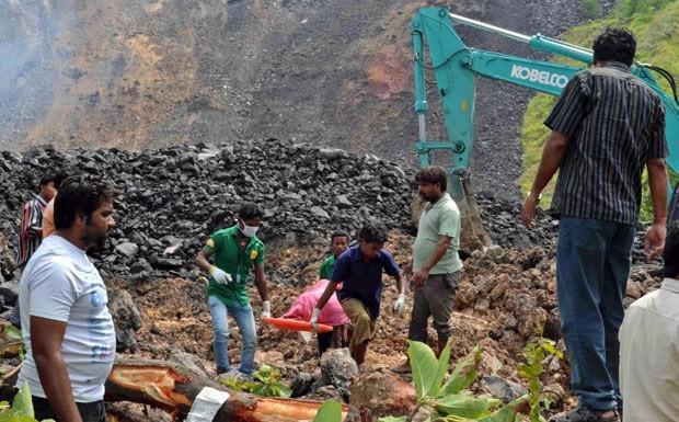 Resgatistas carregam corpo de vítimas de acidente na mina em Sundargarh, na Índia, neste sábado (10) (Foto: AP)