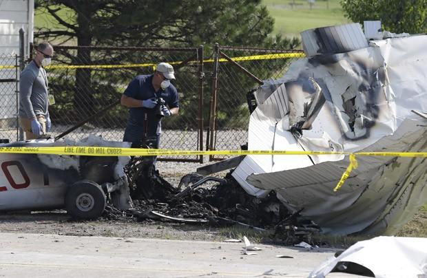 Investigadores fotografam destroços do avião ao lado de uma via em Richmond Heights, no estado americano de Ohio. As quatro pessoas a bordo morreram no acidente (Foto: Tony Dejak/AP)