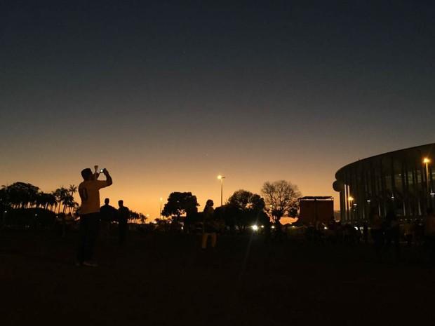 Torcedor faz fotos do estádio Mané Garrincha ao anoitecer, antes da rodada dupla do futebol masculino na Olimpíada (Foto: Alexandre Bastos/G1)
