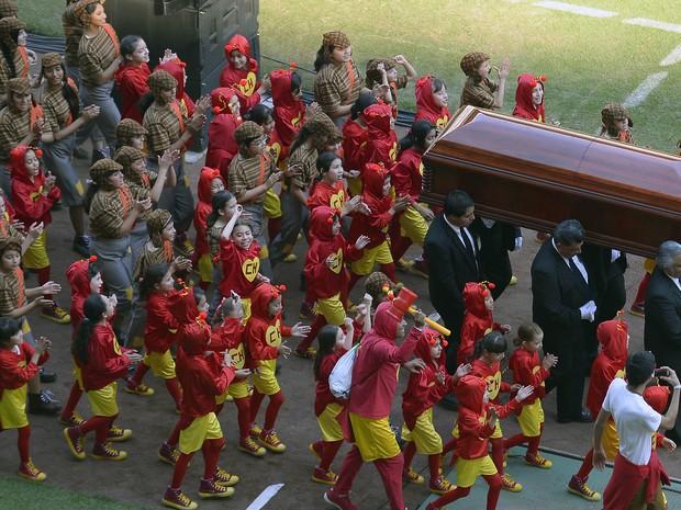 Caixão com corpo de Roberto Bolaños chega ao estádio Azteca rodeado de pessoas vestidas de 'Cahpolin' (Foto: Alfredo Estella/AFP)