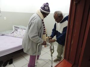 Inácio ajuda a mulher a andar pelo abrigo, em Mogi das Cruzes (Foto: Carolina Paes/G1)