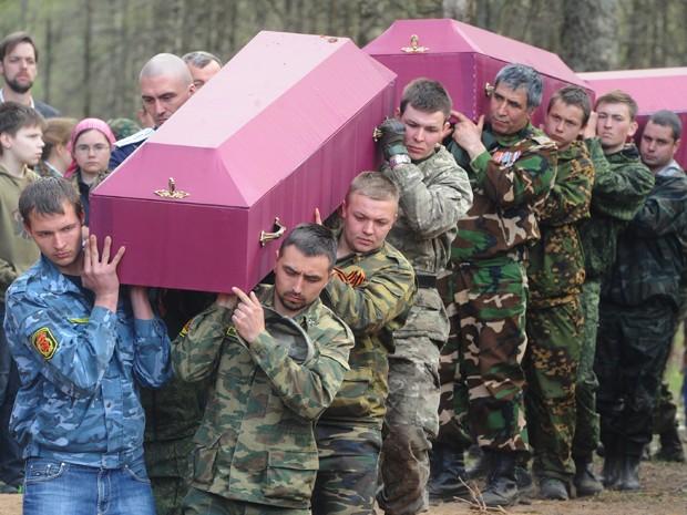 Homens carregam caixões com restos mortais de soldados do Exército Vermelho mortos na II Guerra Mundial, em cerimônia em São Petesburgo, na quinta (7) (Foto: AFP Photo/Olga Maltseva)