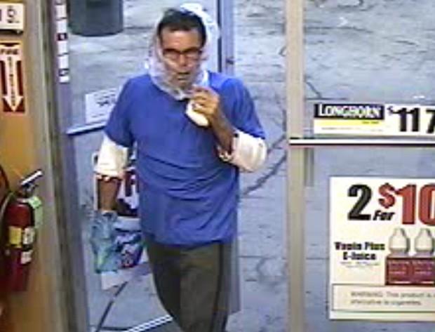 Criminoso entrou no estabelecimento com o rosto parcialmente coberto por sacola plástica e usando outra em uma das mãos, para esconder suposta arma (Foto: Divulgação/Belleville Police Department)