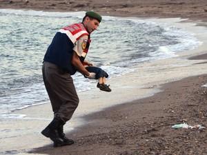 Policial paramilitar recolhe o corpo de uma criança morta que apareceu em praia da ilha de Kos, na Grécia. Vários migrantes morreram afogados e alguns seguem desaparecidos após botes lotados naufragarem durante tentativa de chegar ao território grego