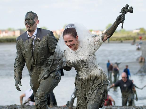 Casal de 'noivos' na anual corrida na lama em Maldon, na Inglaterra, neste domingo (5) (Foto: Leon Neal/AFP)