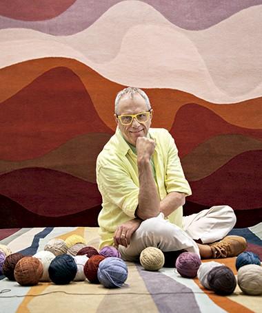Alfredo Barbosa de Oliveira no showroom da Punto e Filo, em São Paulo, sentado em um tapete projetado por ele com fios sintéticos (Foto: Mayra Azzi/ Editora Globo)