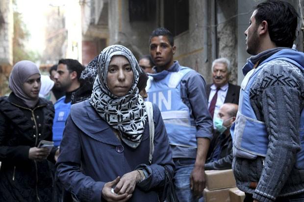 Mulheres sírias recebem comida distribuída pelas Nações Unidas em campo de refugiados de Yarmouk, em Damasco, na Síria, em 10 de março (Foto: Taghrid Mohammed/UNRWA/Handout via Reuters)