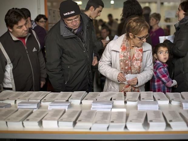 Eleitores escolhem cédulas de voto na Catalunha (Foto: Emilio Morenatti/AP)