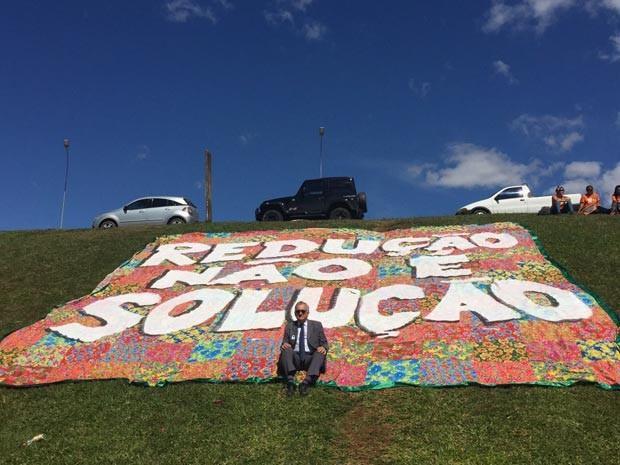 O ministro da Cultura, Juca Ferreira, posa em frente a uma bandeira com mensagens contrárias à redução da maioridade penal (Foto: Luciana Amaral/G1)