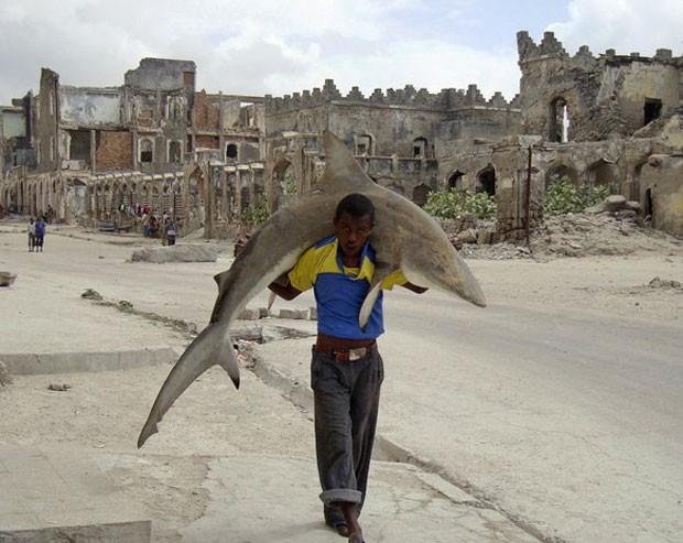 Omar Feisal ganhou um prêmio no 'World Press Photo' de 2010 com uma foto que mostra um pescador carregando um tubarão nos ombros (Foto: Omar Feisal/Reuters)