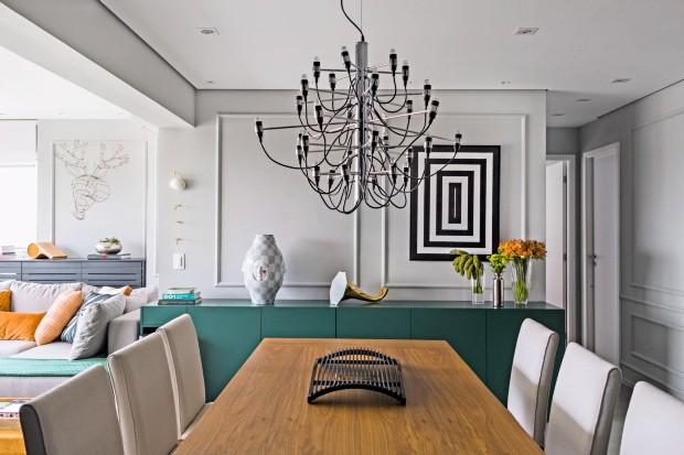 Sala de jantar. O protagonista é o lustre do designer Gino Sarfatti, da Flos, sobre mesa e cadeiras da Clami. Atrás, quadro da Urban Arts e amplificador de som em forma de gramofone da LS Selection (Foto: Edu Castello / Editora Globo)