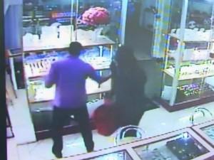 Um dos bandidos obriga vendedora a retirar joias da vitrine (Foto: Reprodução/TV Subaé)