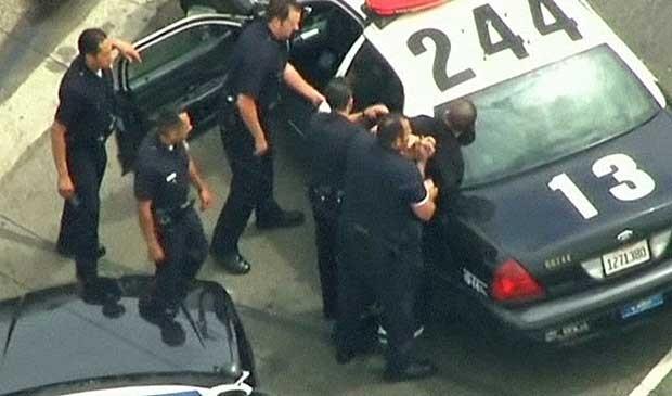Rapaz é levado pelos policiais. (Foto: BBC)