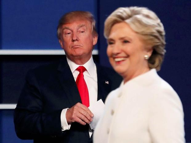 O candidato republicano à Presidência dos EUA, Donald Trump, observa do fundo enquanto sua adversária, a democrata Hillary Clinton, sorri para a plateia ao fim do 3º e último debate presidencial antes das eleições na Universidade de Las Vegas, Nevada (Foto: Mike Blake/Reuters)