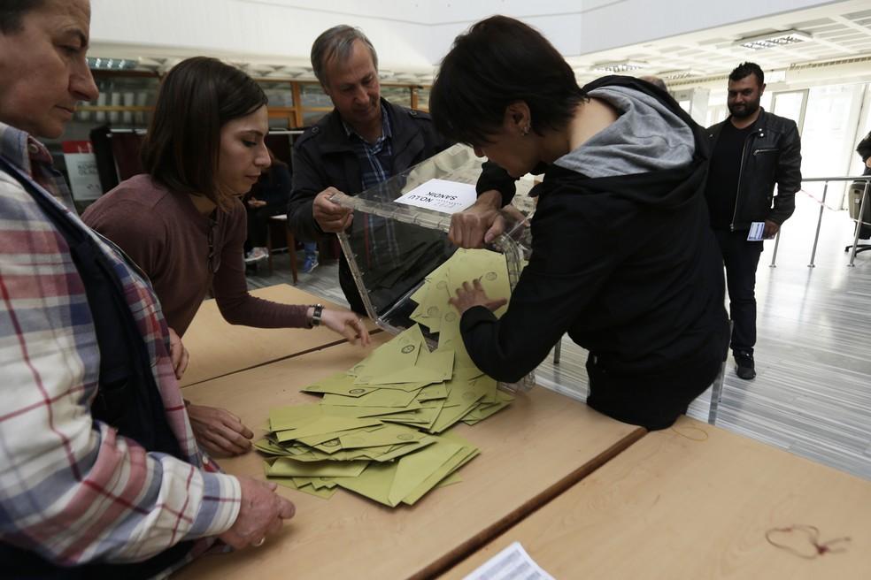 Membros do comitê eleitoral esvaziam uma urna durante o referendo deste domingo (16) em Ankara, na Turquia (Foto: AP/Burhan Ozbilici)