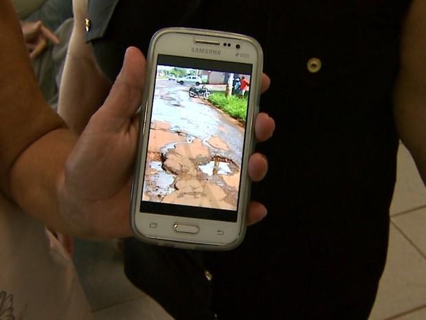 A viúva Valquíria Bíscaro mostra fotos do buraco onde o marido caiu com a motocicleta (Foto: Sérgio Oliveira/EPTV)