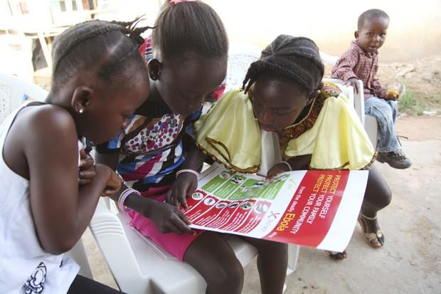 Garotas olham para poster distribuído pela Unicef sobre formas de prevenir a propagação do ebola; atualmente, não há vacina  (Foto:  Reuters/Ahmed Jallanzo/Unicef)