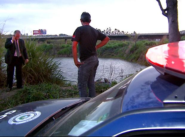 Policiais observam corpo de muher encontrado em mala num lago na região de Campinas (Foto: Reprodução EPTV)