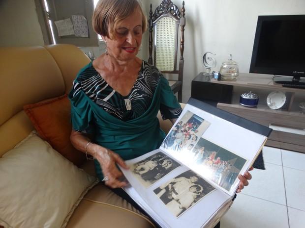 Marinete Lira lembra do São João da Rua 3 de maio ao olhar para as fotografias (Foto: Joalline Nascimento/G1)