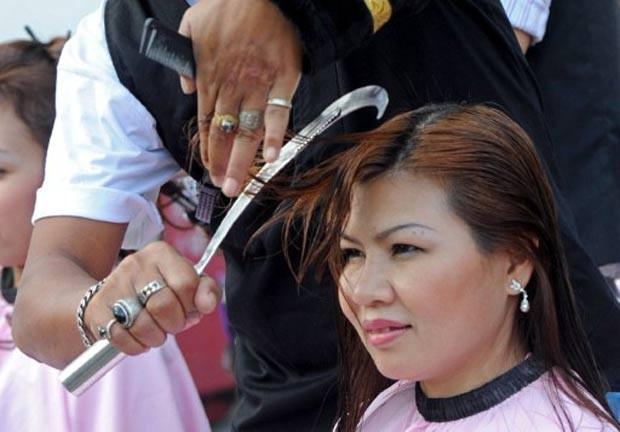 Um cabeleireiro tailandês usa uma foice para cortar o cabelo de clientes em seu salão em Bangcoc, na Tailândia (Foto: Pornchai Kittiwongsakul/AFP)
