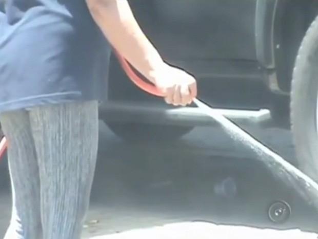 Mulher desperdiça água lavando calçada em Rio Preto (Foto: Reprodução/TV TEM)