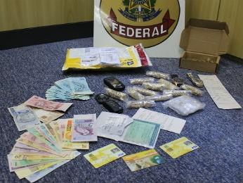 Foto mostra dinheiro, cartões, documentos, relógios e joias que foram encontradas com o funcionário dos Correios (Foto: Divulgação/PF)