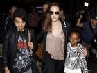 De blusa decotada, Angelina Jolie viaja com os filhos
