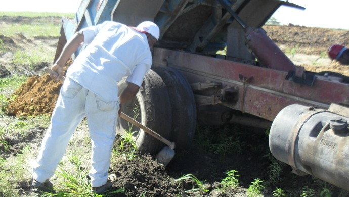 Trabalhadores tentam desatolar caçamba do terreno úmido no Ninho do Galo (Foto: Denison Roma / GloboEsporte.com)