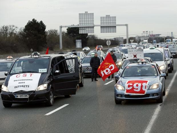 Taxistas bloqueiam a estrada com seus carros perto do Aeroporto de Roissy Charles de Gaulle, perto de Paris, para protestar contra a concorrência dos veículos de transporte turístico (Foto: Thomas Samson/ AFP)