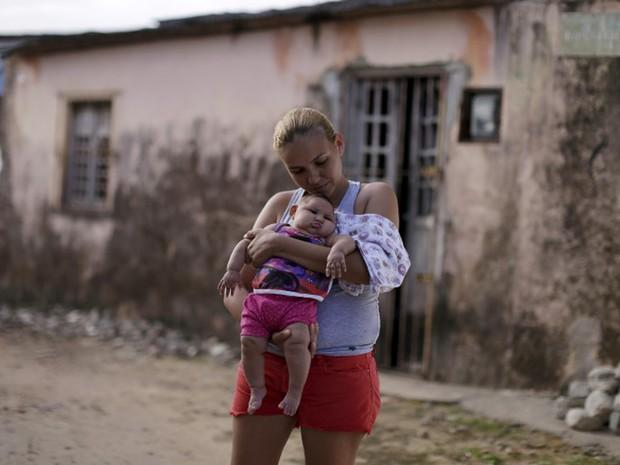 Gleyse da Silva segura a filha com microcefalia diante de sua casa, em Recife  (Foto: Reuters/Ueslei Marcelino)