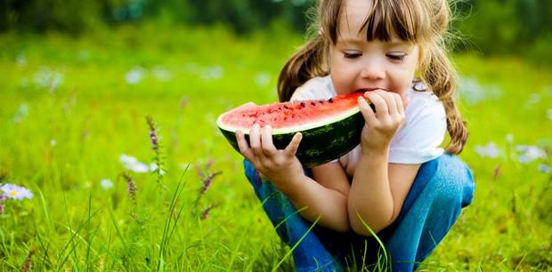 Criança comendo melancia ao ar livre (Foto: Shutterstock)