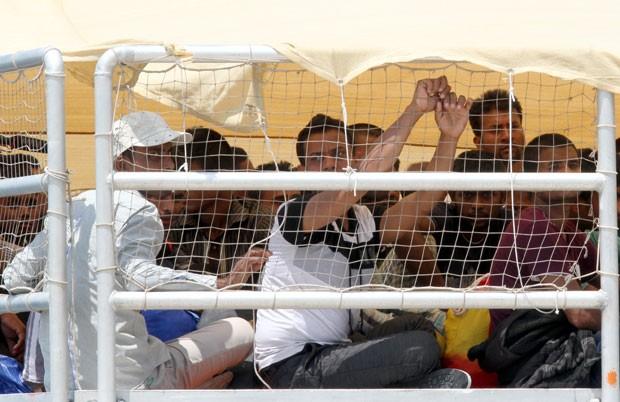 Imigrantes aguardam para desembarcar de navio na Reggio Calabria, Itália, nesta sexta-feira (10) (Foto: Adriana Sapone/AP)