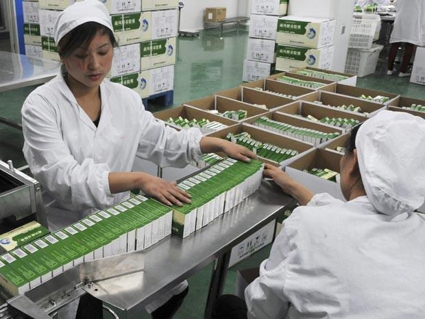 Funcionárias de fábrica chinesa trabalham na produção de medicamentos usados no diagnóstico e no tratamento do H7N9 (Foto: Reuters/China Daily)