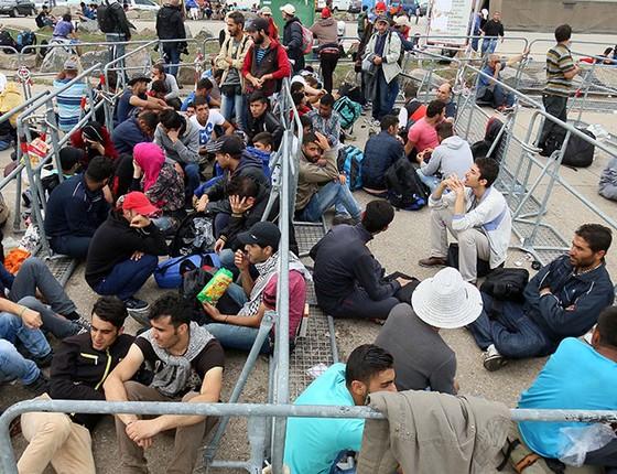 Refugiados esperam para cruzar a fronteira entre a Hungria e a Áustria nesta terça-feira (15) (Foto: AP Photo/Ronald Zak)