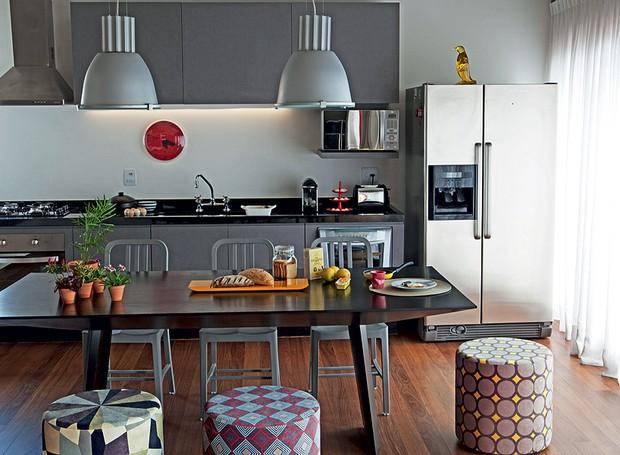 A sala de jantar fica dentro da cozinha deste apartamento de 70 m². Com cadeiras de um lado e pufes do outro, facilita a circulação no ambiente. Projeto da arquiteta Andrea Reis (Foto: Otavio Dias/Casa e Jardim)