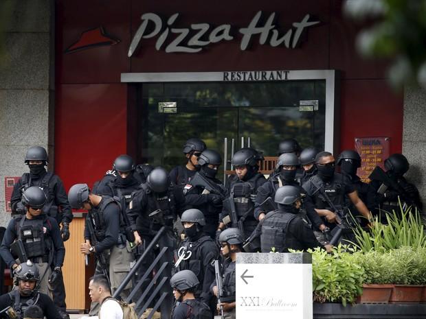 Policiais se concentram do lado de fora de restaurante no centro de Jacarta perto do local onde bombas explodiram nesta quinta-feira, na Indonésia (Foto: REUTERS/Beawiharta)