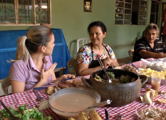Tharyana provando a pucheirada da família Garcia (Foto: TV Morena)