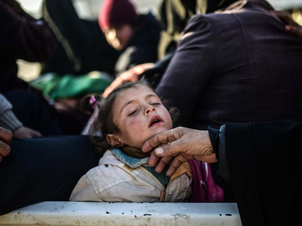 Menina dorme enquanto espera perto da cidade síria de Azaz para passar para a Turquia (Foto: BULENT KILIC / AFP)