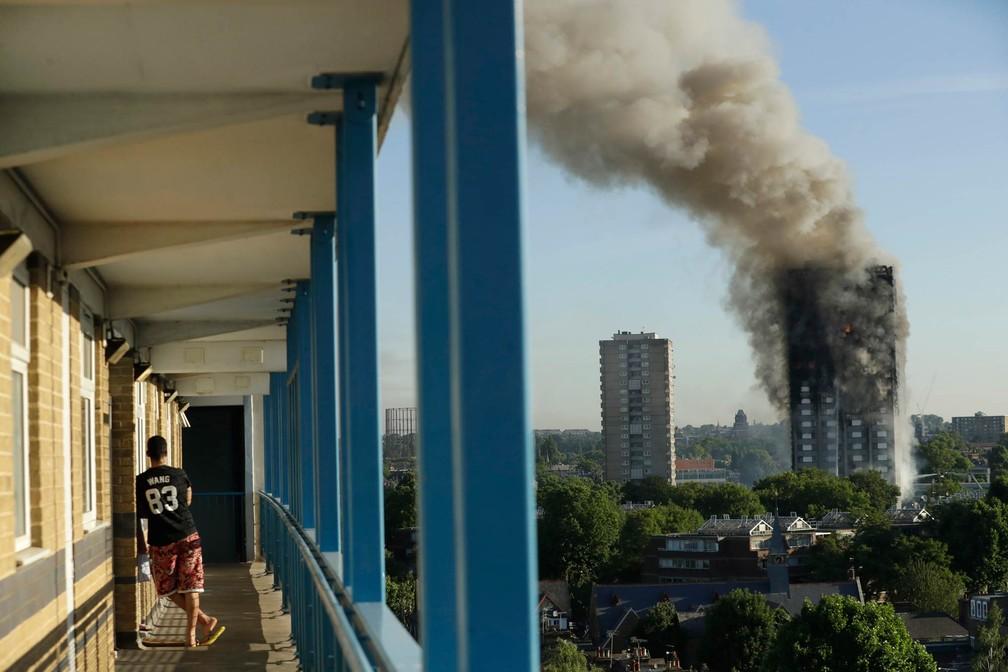 Morador observa de longe o incêndio em prédio no oeste de Londres (Foto: Matt Dunham/AP)