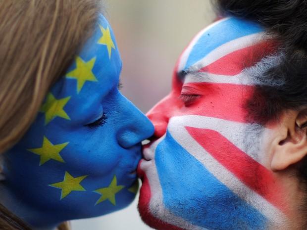 Ativistas com as bandeiras da União Europeia e do Reino Unido pintadas em seus rostos se beijam na frente do Portão de Brandenburgo em Berlim, na Alemanha,para protestar contra a saída britânica da União Europeia (Foto: Hannibal Hanschke/Reuters)