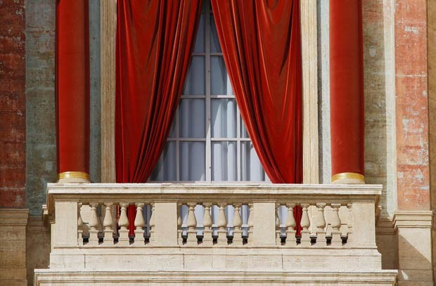 Imagem mostra o balcão central da Basílica de São Pedro, no Vaticano, pronto nesta terça-feira (12), com as cortinas vermelhas, para a primeira bênção do novo Papa; cerca de 10 minutos após o anúncio do 'habemus papam', o novo pontífice aparece no balcão e dá sua primeira bênção 'urbi et orbi' (para a cidade de Roma e para o mundo) (Foto: AFP)
