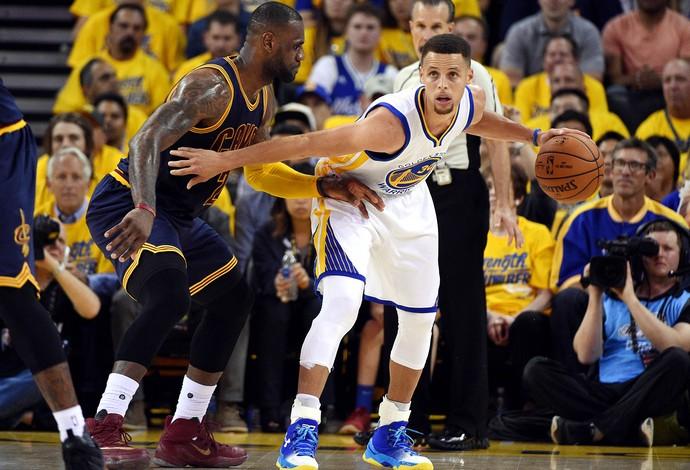 Stephen Curry protege a bola da marcação de LeBron James (Foto: Reuters)