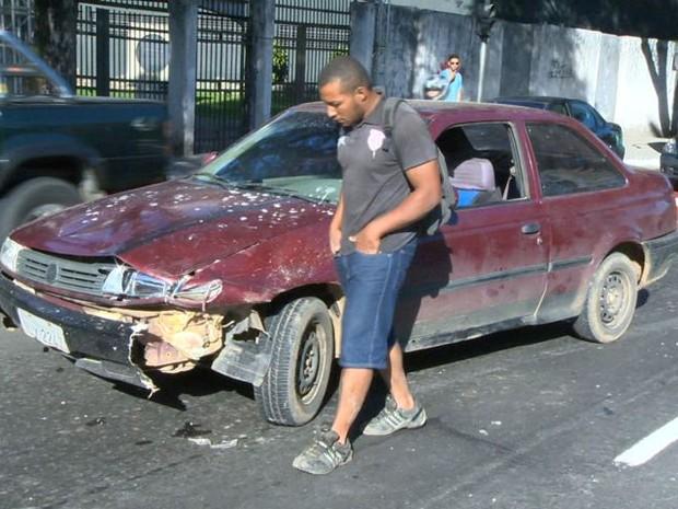 Motorista ao lado do carro que ficou amassado após o acidente (Foto: Reprodução / TV Gazeta)