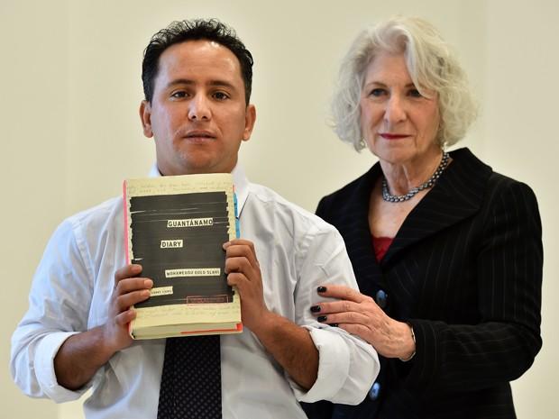 O irmão mais novo do autor e a advogada Nancy Hollander exibem o livro 'Diário de Guantánamo', de Mogamedou Ould Slahi, durante entrevista coletiva em Londres, na terça (20) (Foto: AFP Photo/Ben Stansall)